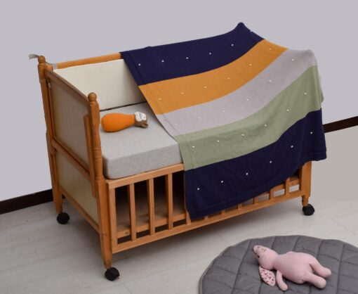 Vauvan peitto värikkäillä raidoilla ja pisteillä